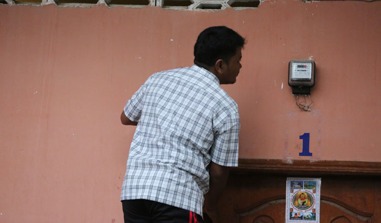 A man checks his power usage on his meter at his home in the capital. KT/Chor Sokunthea
