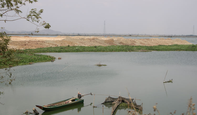 A boat with reclaimed land in the background